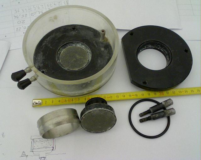 fotografia di cella edometrica, con corpo cella, coperchio, fustella inox, pietre porose